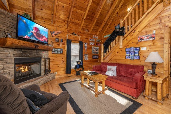 Fireplace and TV in a living room at Nascar Nation, a 2 bedroom cabin rental located in Pigeon Forge