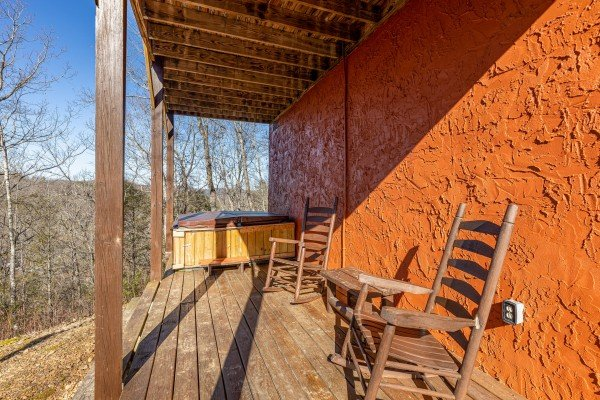 Lower deck with hot tub and rocking chairs at Nascar Nation, a 2 bedroom cabin rental located in Pigeon Forge
