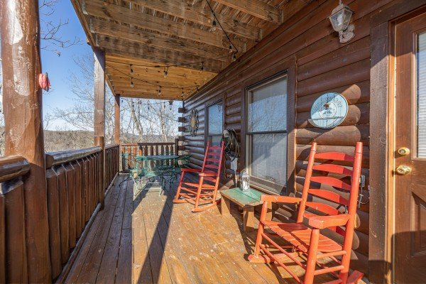 Rocking chairs on a covered deck at Nascar Nation, a 2 bedroom cabin rental located in Pigeon Forge