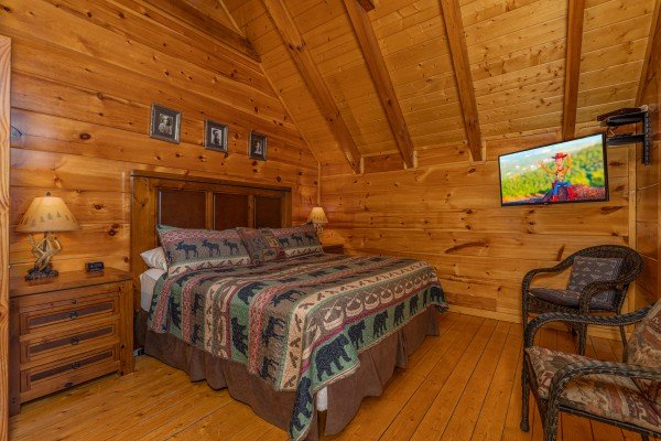 Bedroom with king bed, night stands, lamps, and TV at La Kiara a 3 bedroom cabin rental located in Pigeon Forge