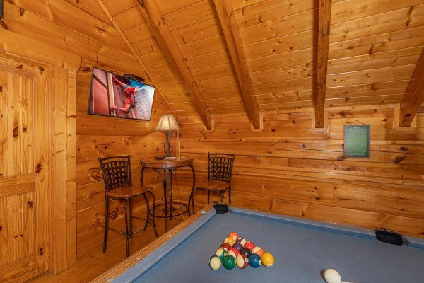 Pool table, TV, and high top bar table in the game loft at La Kiara a 3 bedroom cabin rental located in Pigeon Forge