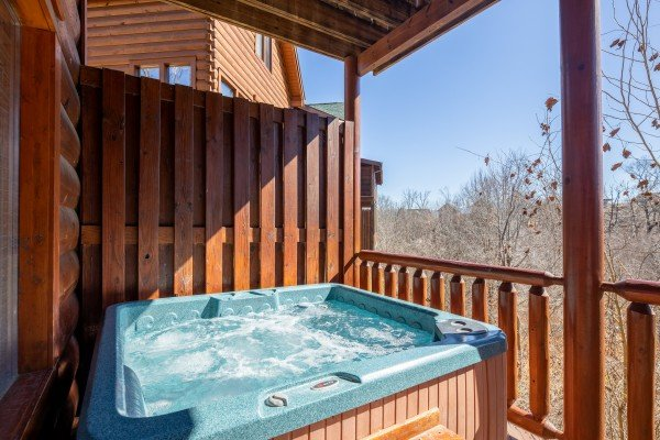 Hot tub on a covered deck with privacy fence at La Kiara a 3 bedroom cabin rental located in Pigeon Forge
