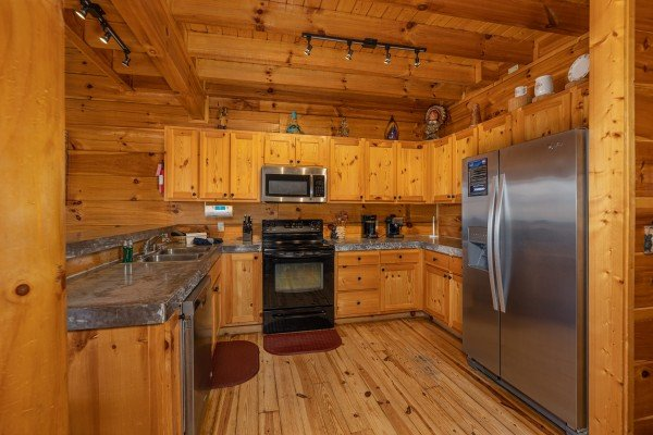 Kitchen with black and stainless appliances at La Kiara a 3 bedroom cabin rental located in Pigeon Forge