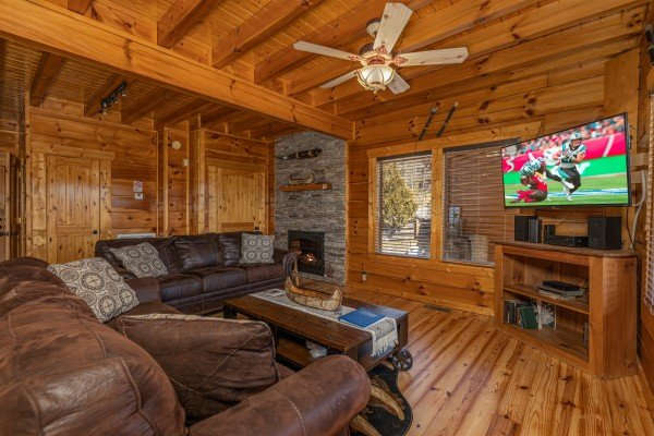 Living room with fireplace and TV at La Kiara a 3 bedroom cabin rental located in Pigeon Forge