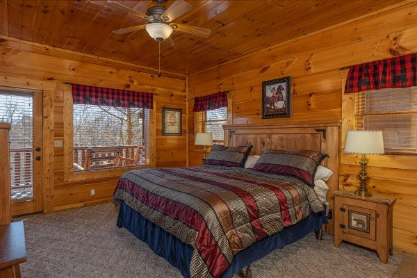 Bedroom with bed, night stands, lamps, and deck access at La Kiara a 3 bedroom cabin rental located in Pigeon Forge
