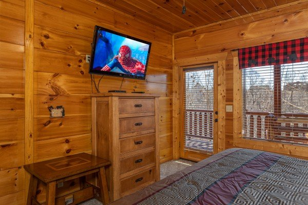 Dresser, TV, and deck access in a bedroom at La Kiara a 3 bedroom cabin rental located in Pigeon Forge