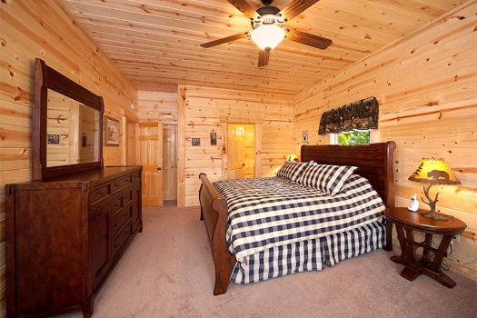 King sized bed with dresser in first floor bedroom at Log Wild! A 4 bedroom cabin rental located in Pigeon Forge