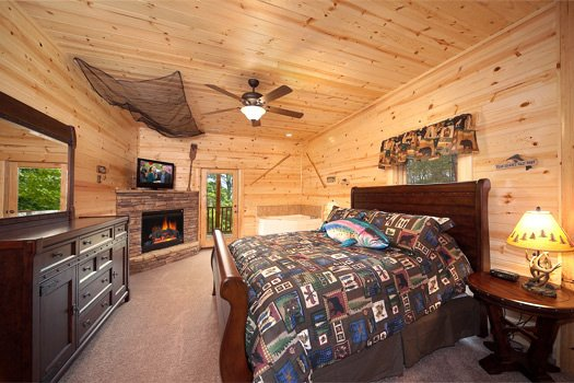 First floor bedroom with dresser and king sized bed at Log Wild! A 4 bedroom cabin rental located in Pigeon Forge