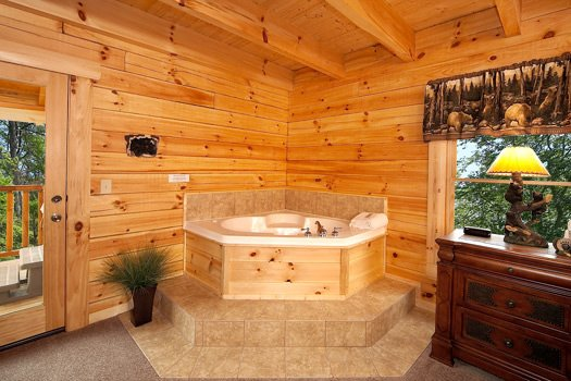 Jacuzzi tub in the corner of the main level bedroom at Log Wild! A 4 bedroom cabin rental located in Pigeon Forge