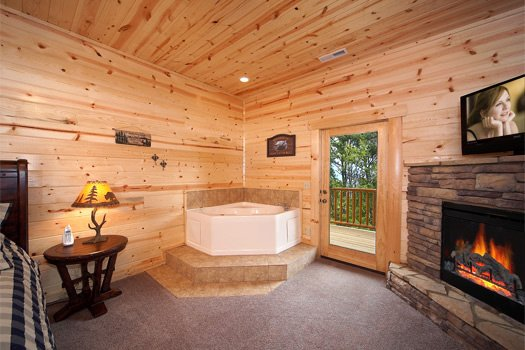 Corner jacuzzi tub next to fireplace in first floor bedroom at Log Wild! A 4 bedroom cabin rental located in Pigeon Forge