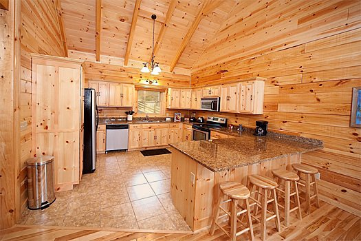 Kitchen with breakfast bar at Log Wild! A 4 bedroom cabin rental located in Pigeon Forge