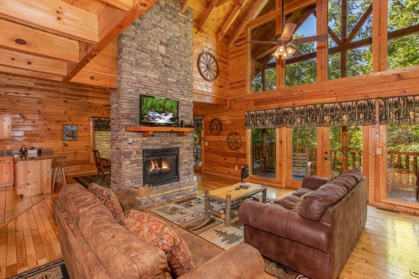 Living room with a see through fireplace and vaulted ceiling with large windows at Log Wild! A 4 bedroom cabin rental located in Pigeon Forge