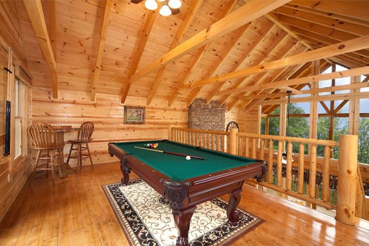 Lofted game room with pool table at Log Wild! A 4 bedroom cabin rental located in Pigeon Forge