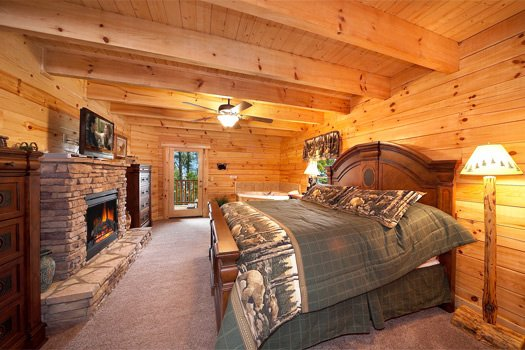 King sized bed in front of stone fireplace in main level bedroom at Log Wild! A 4 bedroom cabin rental located in Pigeon Forge