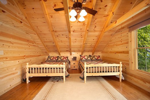 Two full sized beds in a bedroom at Log Wild! A 4 bedroom cabin rental located in Pigeon Forge