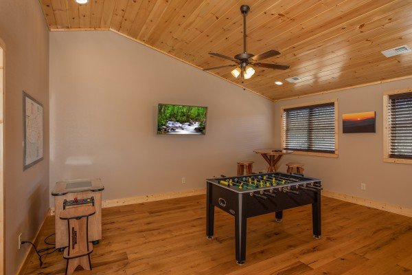 Foosball and arcade game in the game room at Wander Inn Gatlinburg, a 3 bedroom cabin rental located in Gatlinburg
