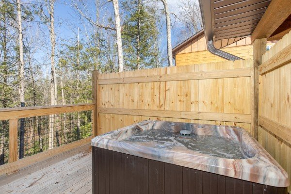 Hot tub and privacy fence on a deck at Wander Inn Gatlinburg, a 3 bedroom cabin rental located in Gatlinburg