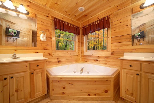jacuzzi tub in the master bathroom between his and her sinks at big sky lodge a 3 bedroom cabin rental located in gatlinburg