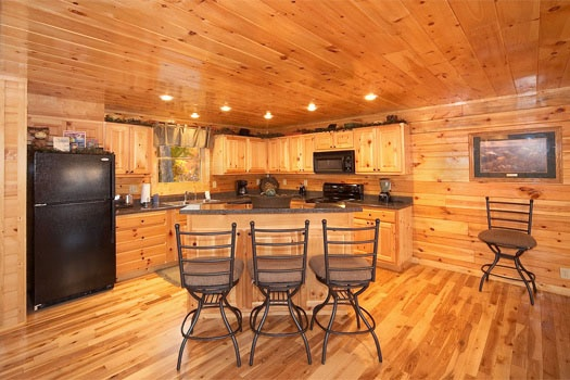 kitchen in the corner with island in front with bar stools at big sky lodge a 3 bedroom cabin rental located in gatlinburg