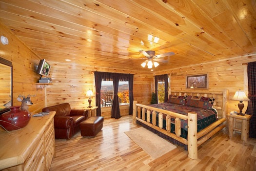 master bedroom with king sized bed with ensuite and deck access at big sky lodge a 3 bedroom cabin rental located in gatlinburg