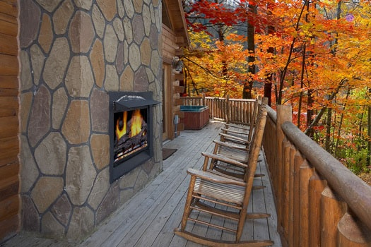 Several rocking chairs around the fireplace on the deck of Big Sky Lodge, a 3-bedroom rental located in Gatlinburg