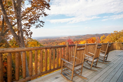 rocking chairs on the deck looking out over the smoky mountains at big sky lodge a 3 bedroom cabin rental located in gatlinburg