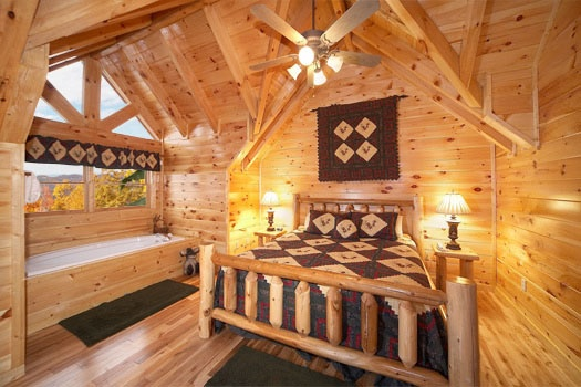 king sized bed with in room jacuzzi tub at big sky lodge a 3 bedroom cabin rental located in gatlinburg