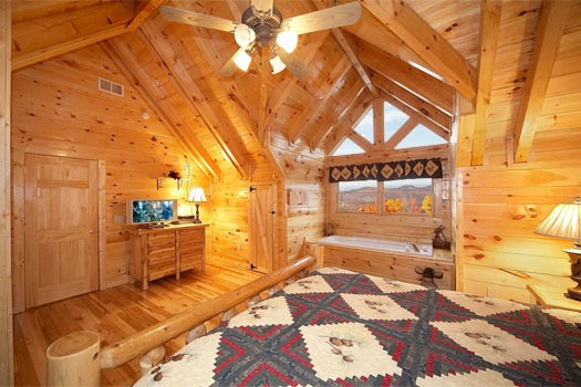 second floor master suite with jacuzzi tub next to log framed king bed at big sky lodge a 3 bedroom cabin rental located in gatlinburg
