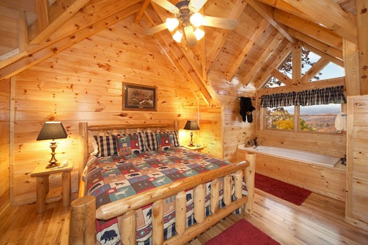 second floor bedroom with king sized bed on a log frame with jacuzzi tub next at big sky lodge a 3 bedroom cabin rental located in gatlinburg