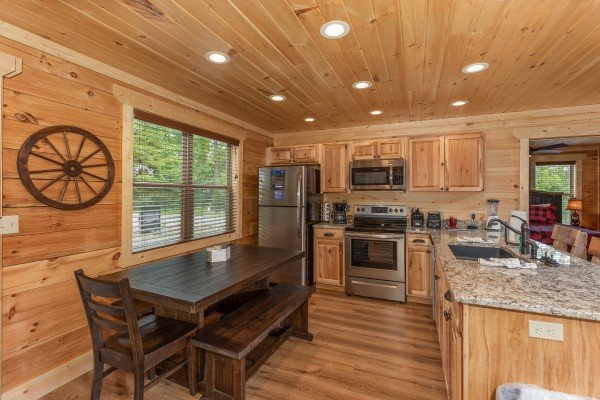 Large dining table in the stainless steel kitchen at Sawmill Springs, a 3 bedroom cabin rental located in Pigeon Forge