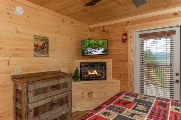 Dresser, fireplace, and TV in a bedroom with deck access at Sawmill Springs, a 3 bedroom cabin rental located in Pigeon Forge