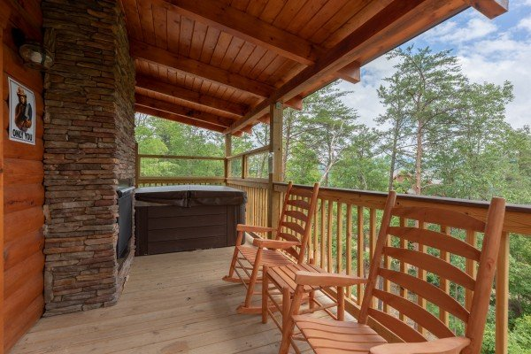 Hot tub, double fireplace, and rocking chairs on a covered deck at Sawmill Springs, a 3 bedroom rental cabin in Pigeon Forge