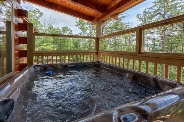 Hot tub on a covered deck at Sawmill Springs, a 3 bedroom rental cabin in Pigeon Forge