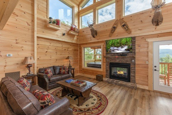 Living room with double-sided fireplace & TV at Sawmill Springs, a 3 bedroom cabin rental located in Pigeon Forge