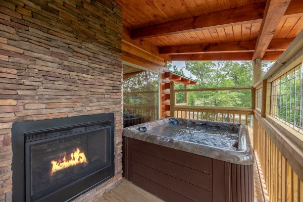 Outdoor fireplace & hot tub on the covered deck at Sawmill Springs, a 3 bedroom rental cabin in Pigeon Forge