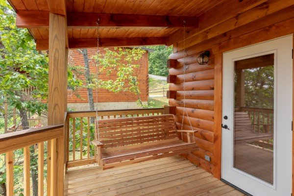 Swing on a covered porch at Sawmill Springs, a 3 bedroom rental cabin in Pigeon Forge