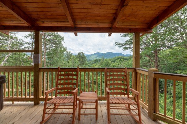 Rocking chairs on a covered deck at Sawmill Springs, a 3 bedroom rental cabin in Pigeon Forge