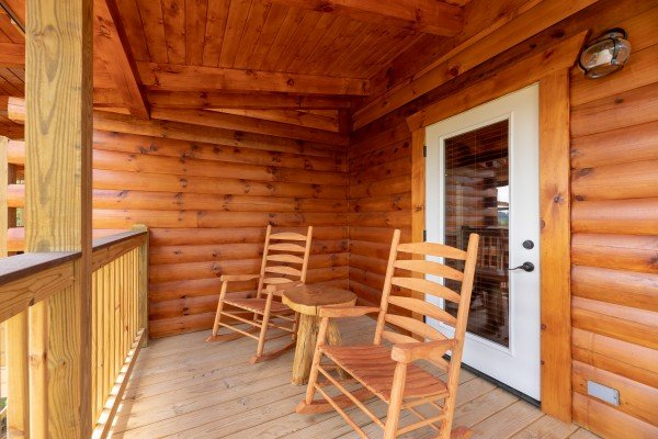 Rocking chairs and a table on the covered deck at Sawmill Springs, a 3 bedroom rental cabin in Pigeon Forge