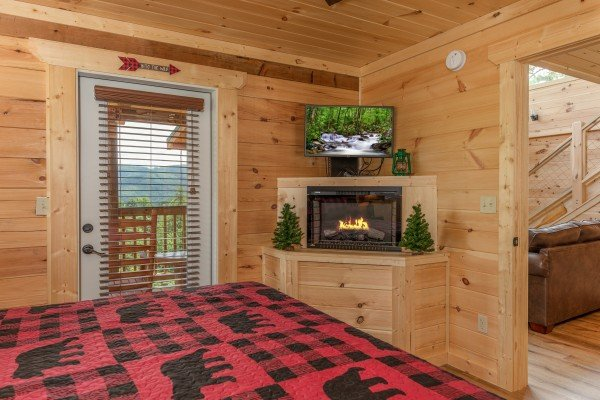 Fireplace, TV, and deck access in a bedroom at Sawmill Springs, a 3 bedroom cabin rental located in Pigeon Forge