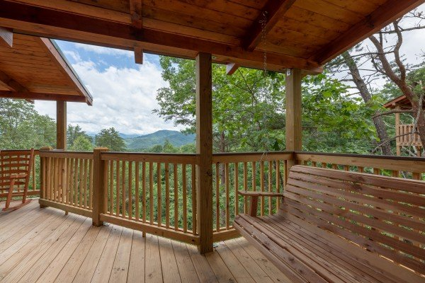 Swing and view from the covered porch at Sawmill Springs, a 3 bedroom rental cabin in Pigeon Forge