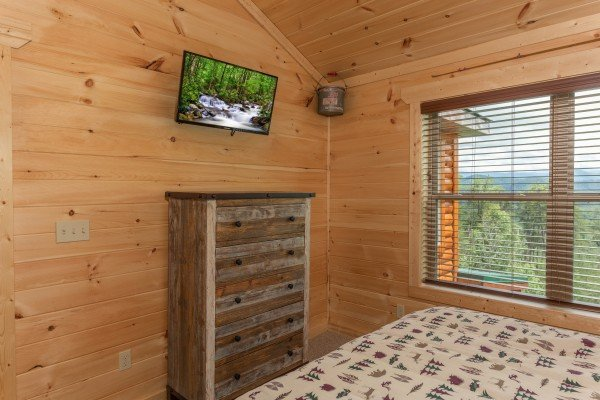 TV and dresser in a bedroom at Sawmill Springs, a 3 bedroom rental cabin in Pigeon Forge