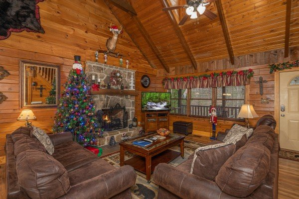 Living room with fireplace, TV, and Christmas decor at Pigeon Forge Pleasures, a 3 bedroom cabin rental located in Pigeon Forge