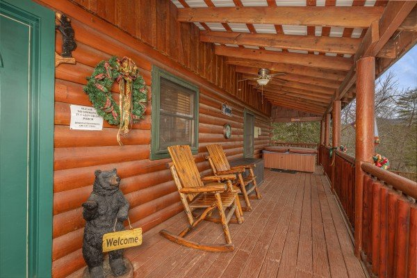 Rocking chairs and hot tub on a covered porch at Pigeon Forge Pleasures, a 3 bedroom cabin rental located in Pigeon Forge