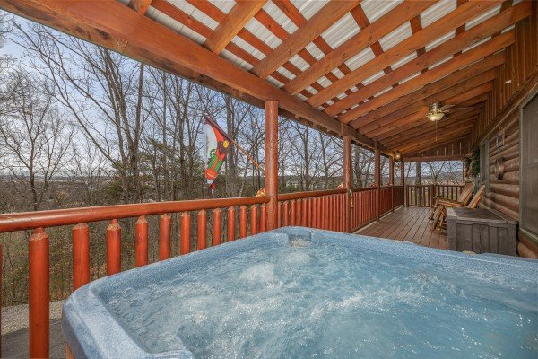 Hot tub on a covered deck with wooded views at Pigeon Forge Pleasures, a 3 bedroom cabin rental located in Pigeon Forge