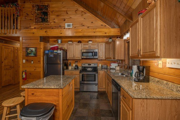 Kitchen with stainless appliances, granite counters, and island at Pigeon Forge Pleasures, a 3 bedroom cabin rental located in Pigeon Forge
