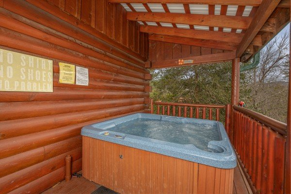 Hot tub on a covered deck at Pigeon Forge Pleasures, a 3 bedroom cabin rental located in Pigeon Forge