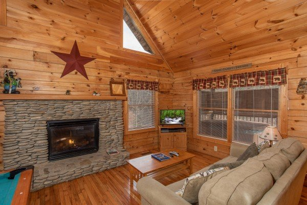 Fireplace and TV in the living room at Bearly Mine, a 1 bedroom Pigeon Forge cabin rental
