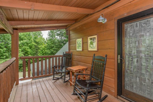 Black rocking chairs and a small table on a covered deck at Aw Paw's Place, a 1-bedroom cabin rental located in Pigeon Forge
