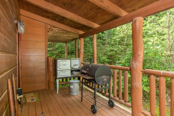Charcoal grill on a covered deck at Aw Paw's Place, a 1-bedroom cabin rental located in Pigeon Forge