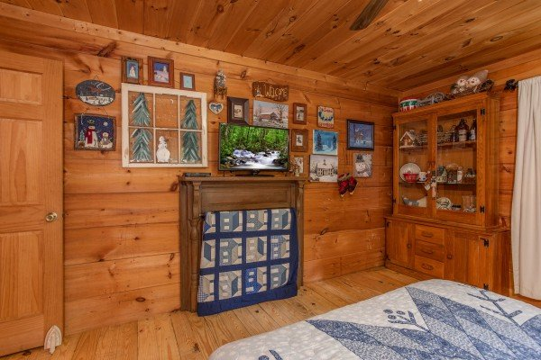Bedroom with a wall mounted television and decorative fireplace at Aw Paw's Place, a 1-bedroom cabin rental located in Pigeon Forge